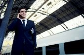 Businessman standing on railway platform using mobile phone, rich man in suit talking on the smart p