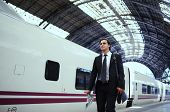 Successful happy businessman walking on the platform ob big railway station, handsome businessman