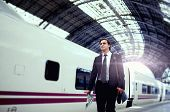 Traveling businessman walking on the big train station, handsome businessman holding newspaper