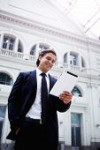 Happy rich businessman using his PC tablet standing in big light hall