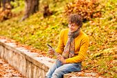 Curly Man In Yellow With Computer Tablet In Autumn