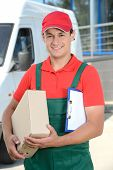 foto of moving van  - Smiling young male postal delivery courier man in front of cargo van delivering boxes - JPG