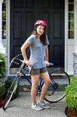 Teenage Girl Outdoors Resting On Her Bicycle While In Front Of Home