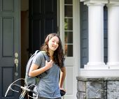 Teenage Girl Outdoors With School Bag And Bicycle In Front Of Home