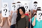 Female Student Surrounded By Classmates Holding Question Mark Signs