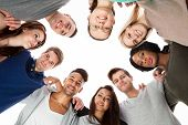 picture of huddle  - Low angle portrait of confident college students forming huddle over white background - JPG
