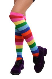 picture of green-blue  - Pretty legs in a crazy combination of multi-colored striped knee-his & chunky purple suede shoes.  Isolated.