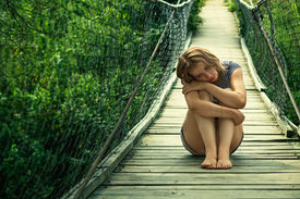 picture of saddening  - Lonely sad girl sitting on the suspension bridge - JPG