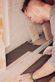 image of ceramic tile  - Tiler installs ceramic tiles at home - JPG