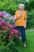 Old Woman With Cane Holding Flowers At The Garden