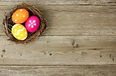 picture of nest-egg  - Easter eggs in a nest over an old wood background - JPG