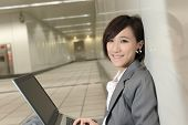 Asian young business woman using laptop and sitting on ground inside modern buildings.
