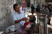 Street Barber Shaving A Man On The Street In Amritsar. India