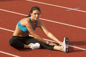 Young Woman in Sports Bra Stretching Leg Muscles on Track