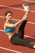 Young Woman in Sports Bra Stretching Leg in the Air on Track