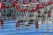 Reflection On The Water Of Table And Red Chairs In Venice Italy