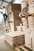 Full length of a warehouse worker loading up pallet