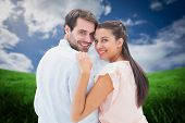 picture of shoulder-blade  - Attractive young couple smiling at camera against green field under blue sky - JPG