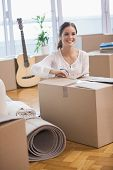 Smiling woman unpacking cardboard boxes in her new home