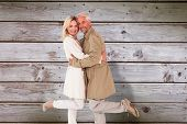 stock photo of trench coat  - Happy couple posing in trench coats against digitally generated grey wooden planks - JPG