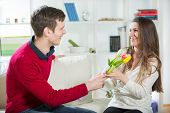 Young guy brings flowers to his girlfriend. Selective focus