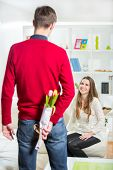 The young man brings flowers to his girlfriend. He's hiding flowers behind their backs.