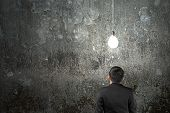 Businessman Looking At Brightly Light Bulb Illuminated Dark Concrete Wall