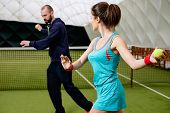 stock photo of  practices  - Woman player and her coach practicing on a tennis court - JPG
