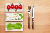 Tomatoes, mozzarella, green salad leaves and silverware on wooden table with copy space