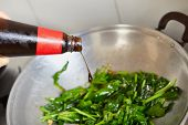 Pouring sauce to the vegetable on the wok. Movement blur while focus on the sauce bottle