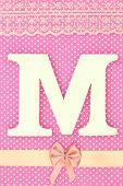 Wooden letter M on polka dots background