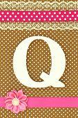 Wooden letter Q on polka dots background