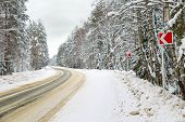 stock photo of slippery-roads  - Danger and fast turn at the icy snow road - JPG