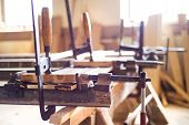 stock photo of carpenter  - Carpenter screw clamp tools pressing planks together - JPG