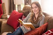 foto of bookworm  - Young woman reading on the couch in her living room - JPG