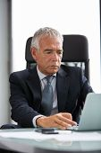 picture of 55-60 years old  - Half length portrait of a thoughtful businessman in the office while using laptop computer - JPG