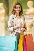 image of shopping center  - Beauty woman with shopping bags in shopping mall is looking at the camera - JPG