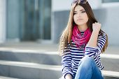 stock photo of straight jacket  - Beautiful young girl, Caucasian appearance, with dark, long, straight hair, brown eyes and beautiful dark eyebrows, wearing a striped shirt, blue jeans, wearing pink neck scarf, sitting outdoors on stairs in the city. ** Note: Shallow depth of field - JPG