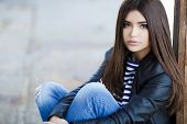 stock photo of black eyes  - Beautiful young girl, Caucasian appearance, with dark, long, straight hair, brown eyes and beautiful dark eyebrows, wearing a striped shirt, blue jeans and black leather jacket, sitting on the street on the sidewalk