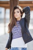picture of straight jacket  - Beautiful young girl, Caucasian appearance, with dark, long, straight hair, brown eyes and beautiful dark eyebrows, wearing a striped shirt, blue jeans and black leather jacket, standing in the street, leaning against a wooden pole. ** Note: Shallow dept - JPG