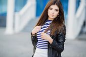 picture of straight jacket  - Beautiful young girl, Caucasian appearance, with dark, long, straight hair, brown eyes and beautiful dark eyebrows, wearing a striped shirt, blue jeans and black leather jacket, standing in the street, near the blue building with white railings