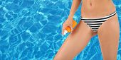 Young woman with slim body in swimsuit on swimming pool water background