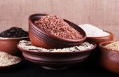 Different kinds of rice in bowls on table on sackcloth background