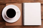 Cup of coffee on saucer with notebook on wooden table background