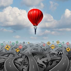 stock photo of leadership  - Easy way forward rise above confusion leadership concept with a businessman in a balloon flying and soaring over a complicated group of roads as a business metaphor of innovative creative thinking for success - JPG