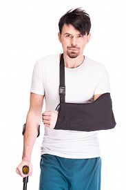 foto of crutch  - Young man with broken leg and hand is using crutch isolated on white background - JPG