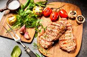 foto of veal  - Grilled veal steaks with vegetables on cutting board - JPG