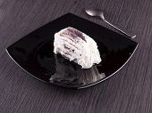 picture of ice-cake  - Slice of ice cream cake over black plate wooden table horizontal image - JPG