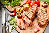 picture of veal  - Grilled veal steaks with vegetables on cutting board - JPG