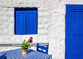 image of greek  - Iconic blue table with wooden chairs and window in front of Greek house - JPG